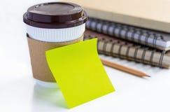 Kaffeetasse- und Papieranmerkung über weiße Tabelle Stockbild