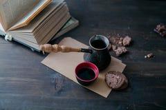Kaffeetasse und Plätzchen und Kaffeemaschine sind auf dem Holztisch nahe bei dem Buch lizenzfreies stockfoto