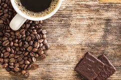 Kaffeetasse und Schokoladen auf einem Holztisch lizenzfreie stockfotografie