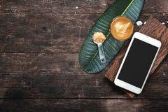Kaffeetasse und Smartphone auf Holztisch Stockfotos