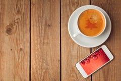 Kaffeetasse und Smartphone mit Weihnachtsbild Weihnachtsfeiertagsfeier Stockfotografie