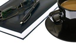 Kaffeetasse und Tagesordnung mit Feder und Gläsern. Stockbild