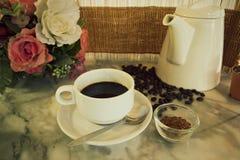 Kaffeetasse und Topf auf Marmortabelle Stockfotos