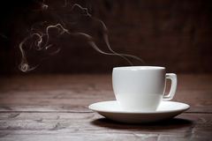 Kaffeetasse und untertasse auf altem Holztisch Stockbilder