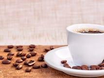 Kaffeetasse und untertasse auf einem Holztisch mit Bohnen Stockbilder