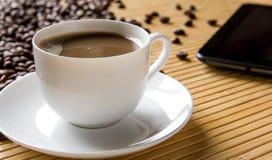 Kaffeetasse und untertasse auf einer hellen Bambustabelle Lizenzfreie Stockbilder