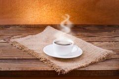 Kaffeetasse und untertasse auf Holztisch. Lizenzfreies Stockfoto