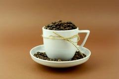 Kaffeetasse und untertasse mit einem Bogen und Kaffeebohnen Lizenzfreie Stockfotos