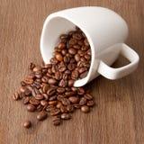 Kaffeetasse und verschüttete Kaffeebohnen lizenzfreies stockfoto