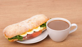 Kaffeetasse und wirkliches Sandwich mit geräuchertem Lachs, Eiern und Grün auf einem hölzernen Hintergrund. Stockbilder
