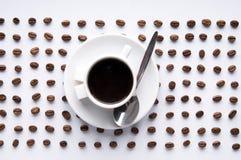 Kaffeetasse und Zeilen der Körner Lizenzfreie Stockfotos