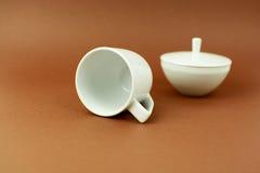 Kaffeetasse und Zuckerschüssel, die auf braunen Hintergrund legt Lizenzfreie Stockfotografie