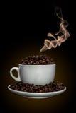 Kaffeetasse voll Kaffeebohnen mit Rauche Stockfotografie