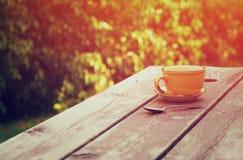 Kaffeetassebecher über Holztisch draußen, zur Nachmittagszeit Selektiver Fokus lizenzfreie stockfotografie