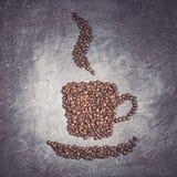 Kaffeetasseform von gebratenen Bohnen mit Dampf auf einem violetten Steinhintergrund stockbilder