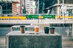 Kaffeetassen auf Betonplatte auf einer Straße Stockbilder