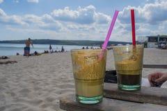 Kaffeetassen auf dem Strand Stockfoto