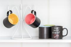 Kaffeetassen auf einem weißen Aufhänger Lizenzfreie Stockfotos