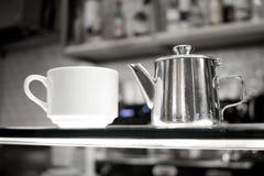 Kaffeetassen auf Glaszähler Stockfoto