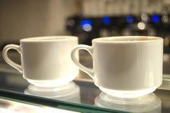 Kaffeetassen auf Glaszähler Stockbilder