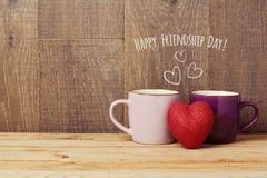 Kaffeetassen auf Holztisch mit Herzform Freundschaftstagesfeier Lizenzfreies Stockfoto