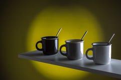 Kaffeetassen mit Löffel auf gelbem Hintergrund lizenzfreie stockfotos