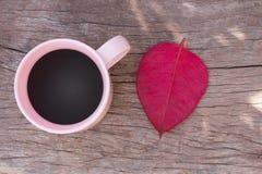 Kaffeetassen mit rosa Draufsicht über Bretterboden und die Rotblätter Lizenzfreies Stockfoto