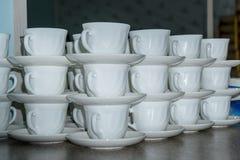 Kaffeetassen mit Untertassen in den Stapeln stockbild