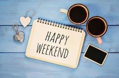 Kaffeetassen nahe bei Notizbuch mit glücklichem Wochenende der Phrase Lizenzfreie Stockfotografie
