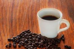 Kaffeetassen und Kaffeebohnen auf hölzernen Brettern Stockfoto