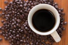 Kaffeetassen und Kaffeebohnen auf hölzernen Brettern Stockbilder