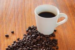 Kaffeetassen und Kaffeebohnen auf hölzernen Brettern Lizenzfreie Stockfotos