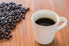 Kaffeetassen und Kaffeebohnen auf hölzernen Brettern Lizenzfreies Stockfoto