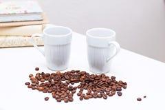 Kaffeetassen und Kaffeebohnen im weißen Stand auf dem Tisch zu Hause Stockfoto