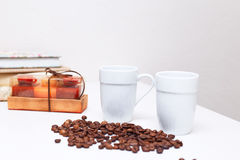 Kaffeetassen und Kaffeebohnen stehen auf der weißen Tabelle Stockbilder