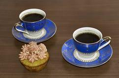 Kaffeetassen und kleiner Kuchen auf Holztisch Stockfotografie