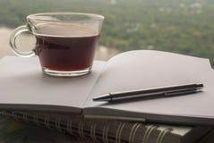 Kaffeetassen und Tagebuch im Flussuferraum lizenzfreie stockbilder