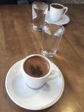 Kaffeetassen und Wasser auf Holztisch Stockbild