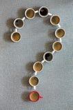 Kaffeetassen vereinbart als Fragezeichen Stockfotografie