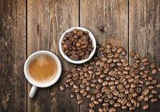 Kaffeetassen voll frischer Espresso und Bohnen auf Holztisch Lizenzfreie Stockfotografie
