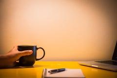 Kaffeetassenotizbuch und -laptop auf Tabelle mit Lampe in der Nacht, Stockbild