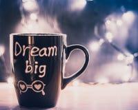 Kaffeetassetraum groß mit Dampf auf einer hölzernen Spitze und Weihnachtslichtern auf einem Hintergrund Copyspace Lizenzfreie Stockfotos