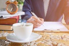Kaffeetasseuhr und -zeitung arbeiten an Tabelle Stockfotos