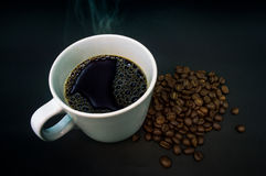 Kaffeetasseweiß mit Rauche auf schwarzem Hintergrund Lizenzfreie Stockfotografie