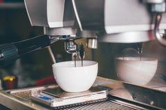 Kaffeextraktion som häller in i en kopp från yrkesmässig kaffemor royaltyfri fotografi