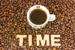 Kaffeezeitfoto Becher mit gebrautem Kaffee wird durch gebratenen ganzen KornKaffeebaum mit der Wortzeit umgeben, gebildet von 3D  Lizenzfreie Stockfotos