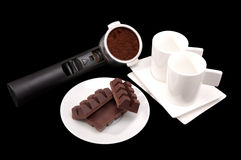 Kaffehållare, kaffe, koppar och tefat och platta med choklad Arkivbilder
