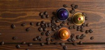 Kaffekapsel med kaffebönor på trätabellen Arkivbild