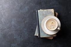Kaffekopp över böcker Arkivbilder