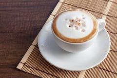 Kaffekopp av cappuccino på bambu som är matt, på träbakgrundsintelligens Arkivfoto